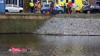 Omstanders halen man uit te water geraakte auto Schiedam