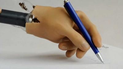 Foto van handprothese schrijvend | TU Delft