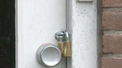 Foto van hangslot op voordeur woning | Archief EHF