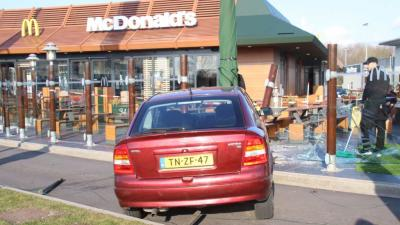 Automobilist rijdt met auto terras McDonald's op