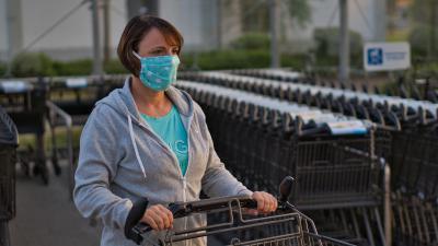 Vrouw met mondkapje en winkelwagen
