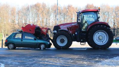 Auto duikt onder grasmaaier van landbouwvoertuig