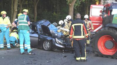 Vrouw in auto bekneld na aanrijding met tractor