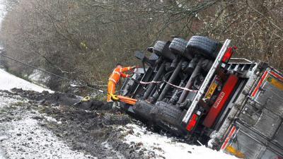 Truck met oplegger glijdt van de weg sloot in