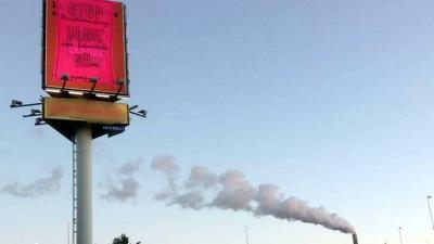Spandoek op reclamezuil naast kolencentrale NUON
