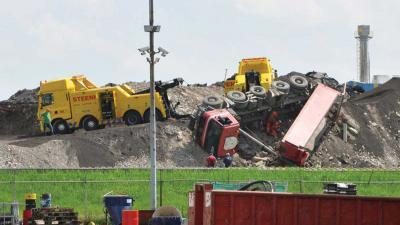 Vrachtwagen valt van puinberg bij afvalverwerker