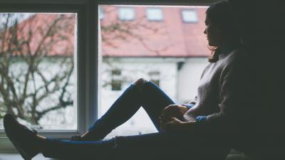 Sombere vrouw kijkt uit raam